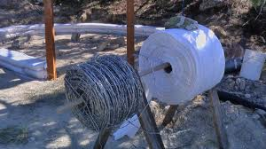 Armed With A Roll Of Polyethylene Bags From The Cal Earth Insute In California Or Common Storage For Fruit And Grains Barbed Wire